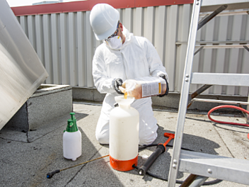 Man with safety mask using hazardous cleaning chemicals