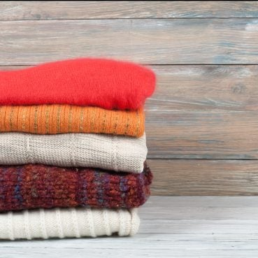 colourful clothes fibres stacked on a wooden background